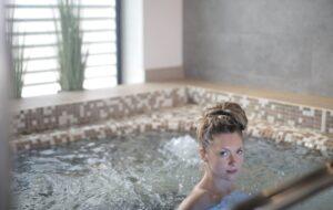 Een vrouw in een warm whirlpool bad dat bubbels genereerd